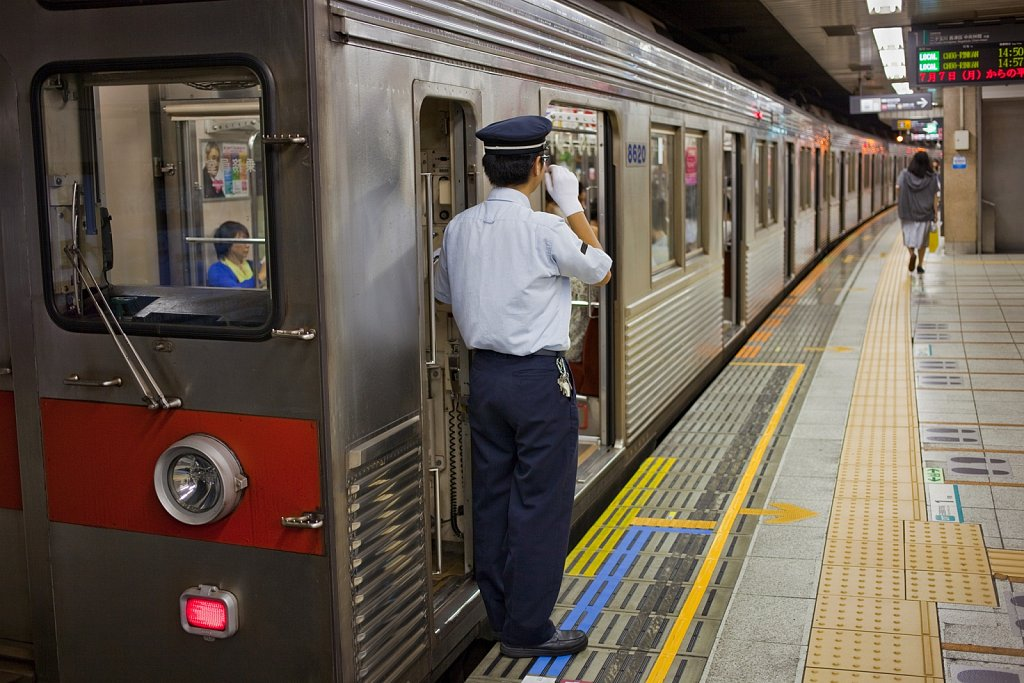 Subway line conductor signals at station in Tokyo, Japan