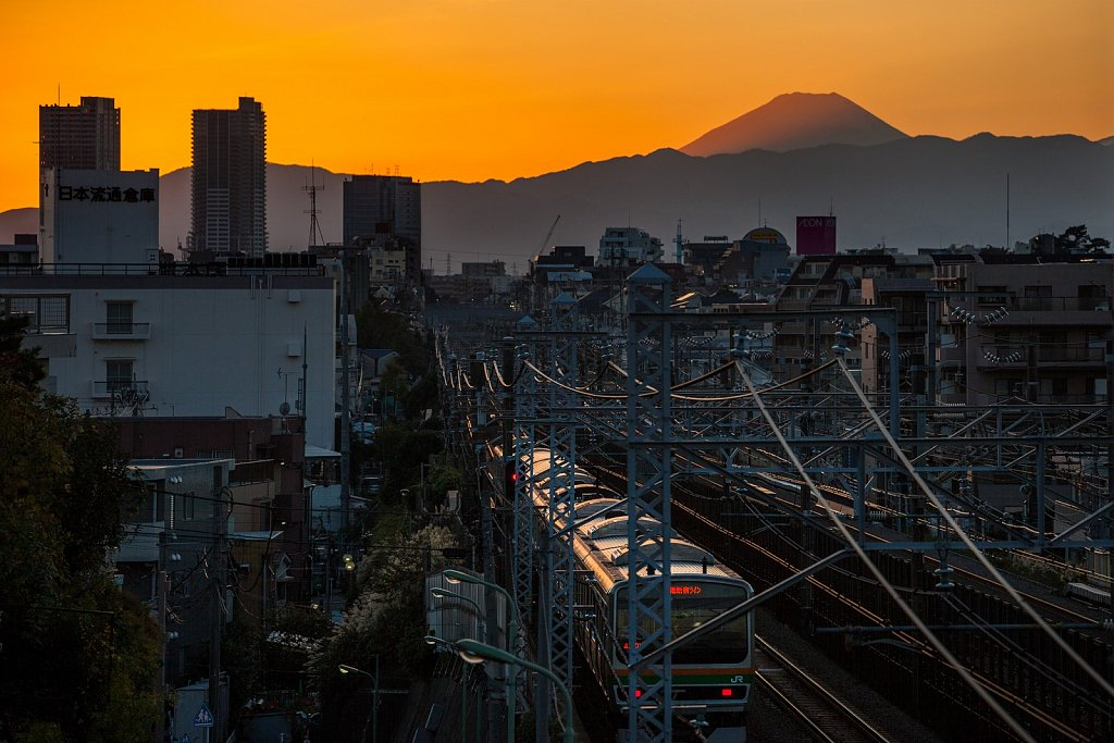 Local train inbound at sunset and Mt Fuji background in Ota-Ku, Tokyo, Japan