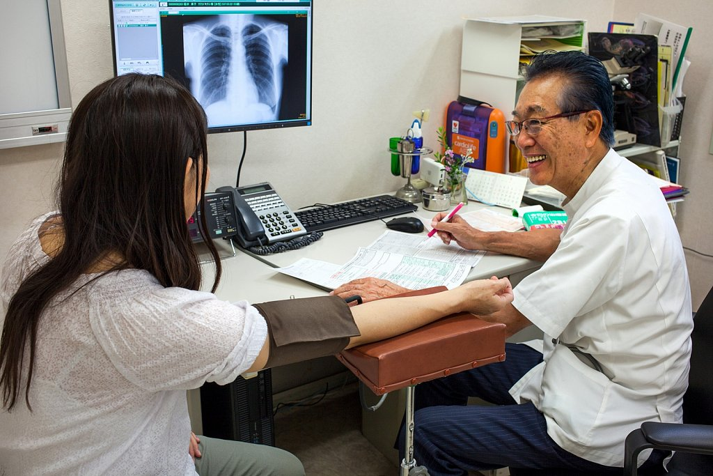 Doctor takes patients blood pressure at medical clinic, Ota, Tokyo, Japan