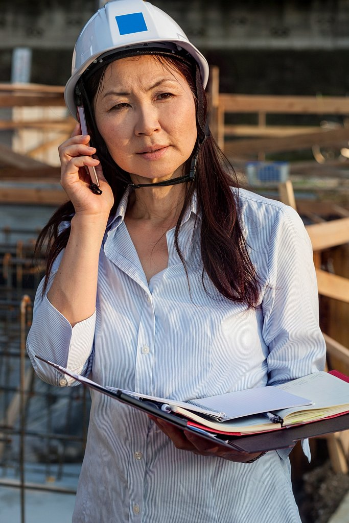 Architect on the phone, checks building site, Nakaikegami, Tokyo, Japan