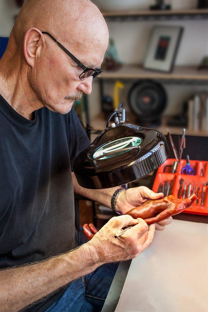 Artist in studio works on wax model for sculpture