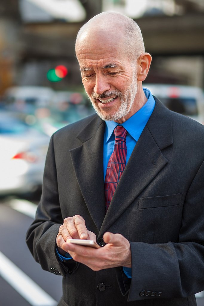 Businessman uses cellphone for texting, Roppongi, Tokyo, Japan