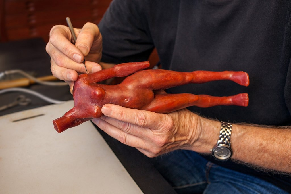 Close up of artists hands working on wax model for sculpture