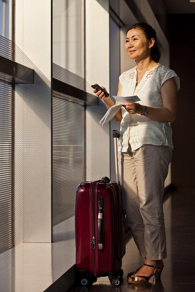 Mature woman checks air ticket at airport, Tokyo, Japan