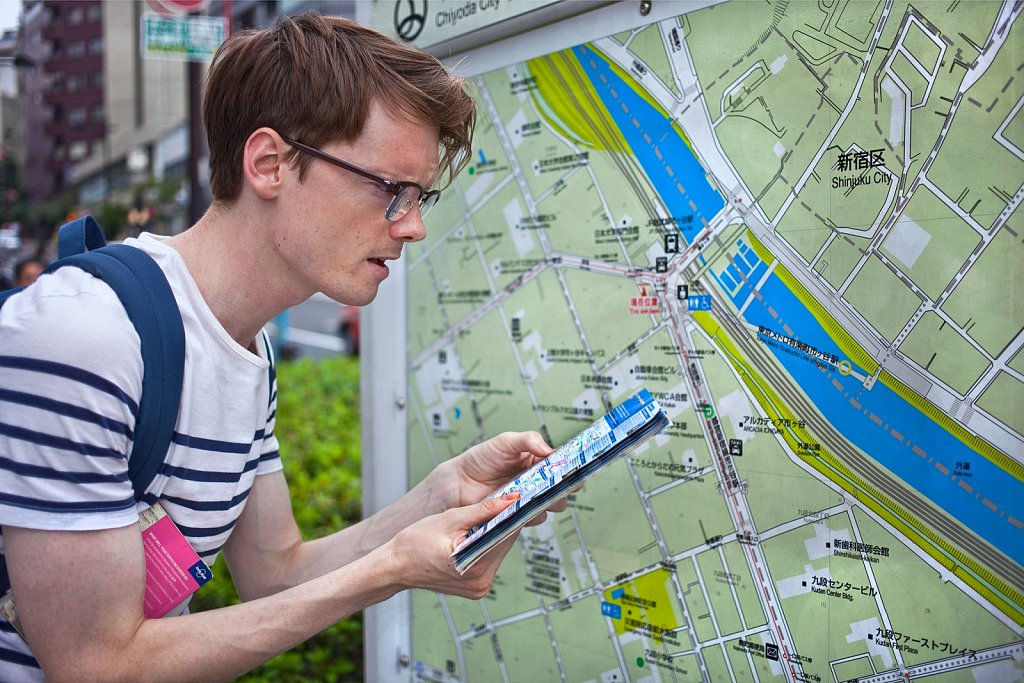 Tourist from Australia checks map in Shinjuku, Tokyo, Japan