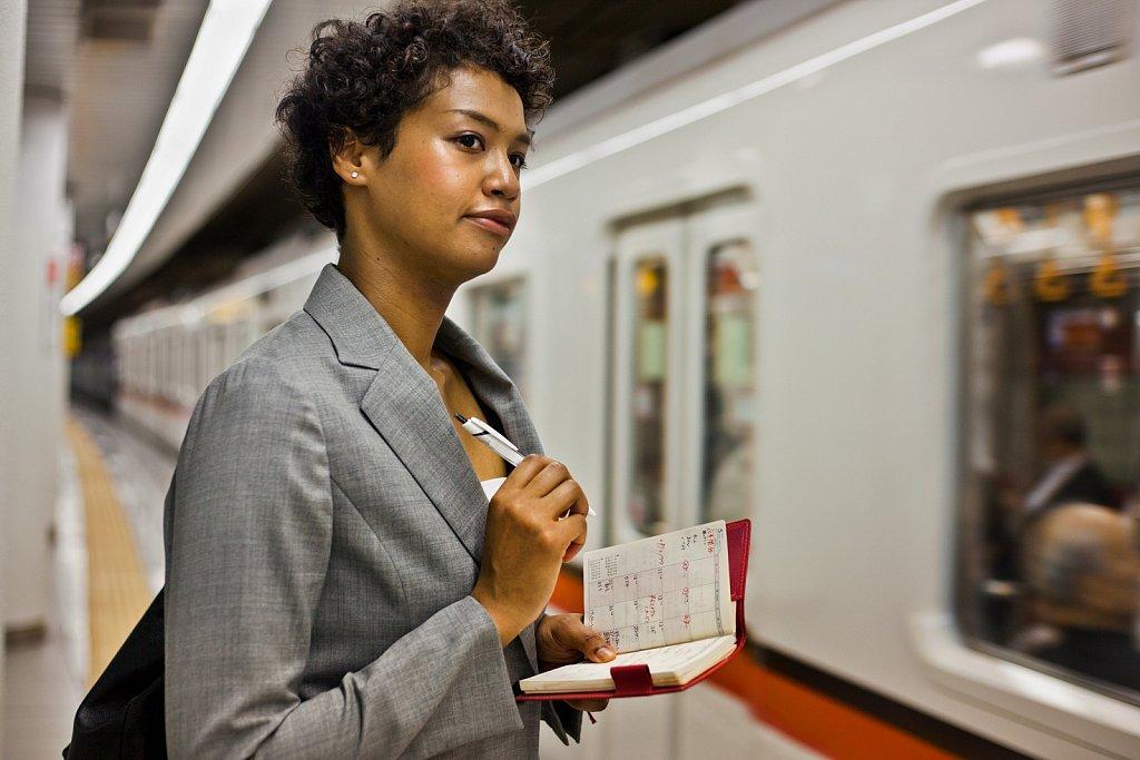Young woman waits for subway train in Gotanda, Tokyo, Japan