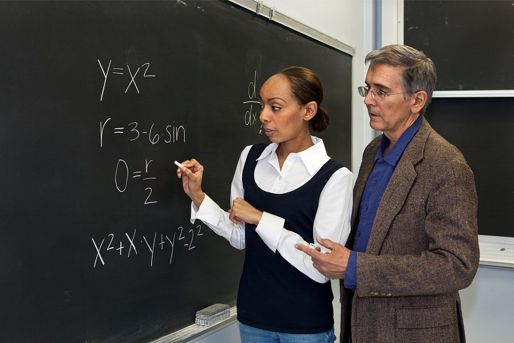 Professor and grad student at classroom blackboard