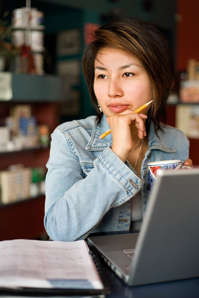 Young Japanese woman at a coffee shop with laptop