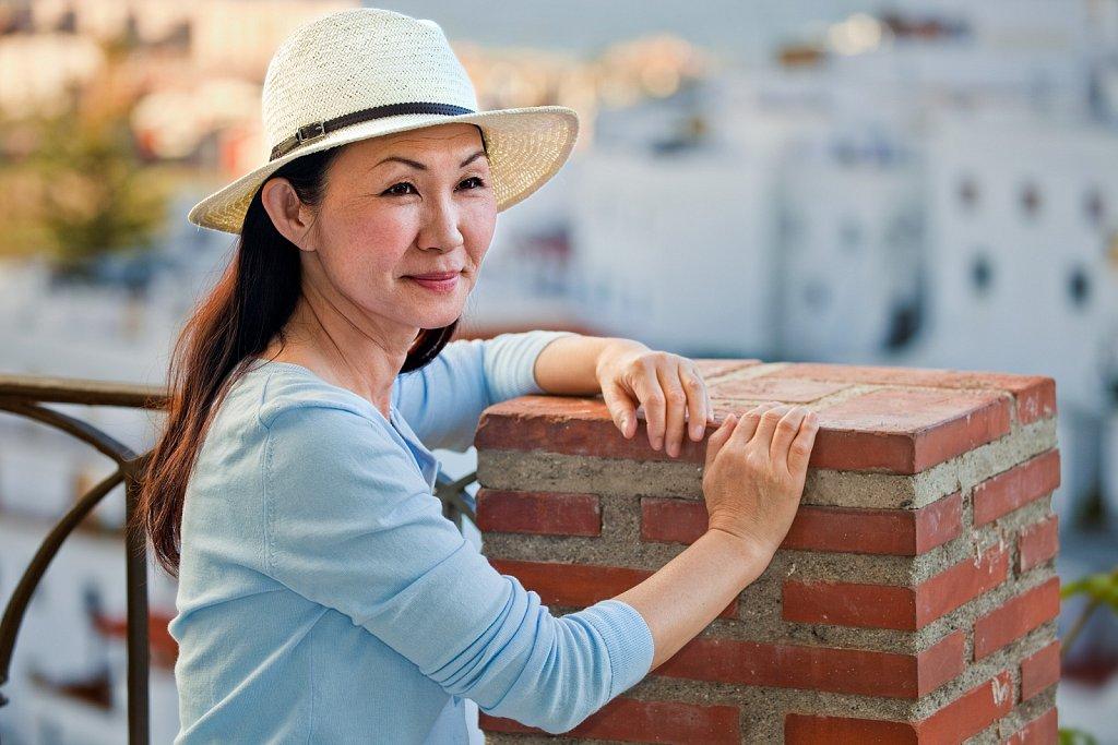Mature Japanese woman tourist in hat, Salobrena, Granada, Spain