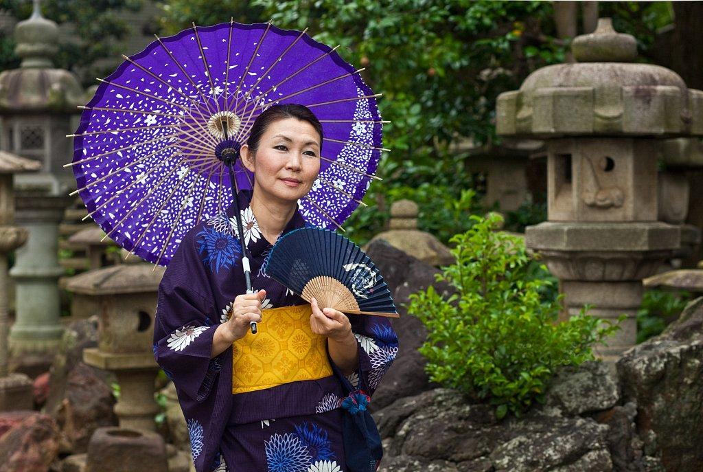 Mature woman in yukata with fan and umbrella at a Temple in Nakaikegami, Tokyo, Japan