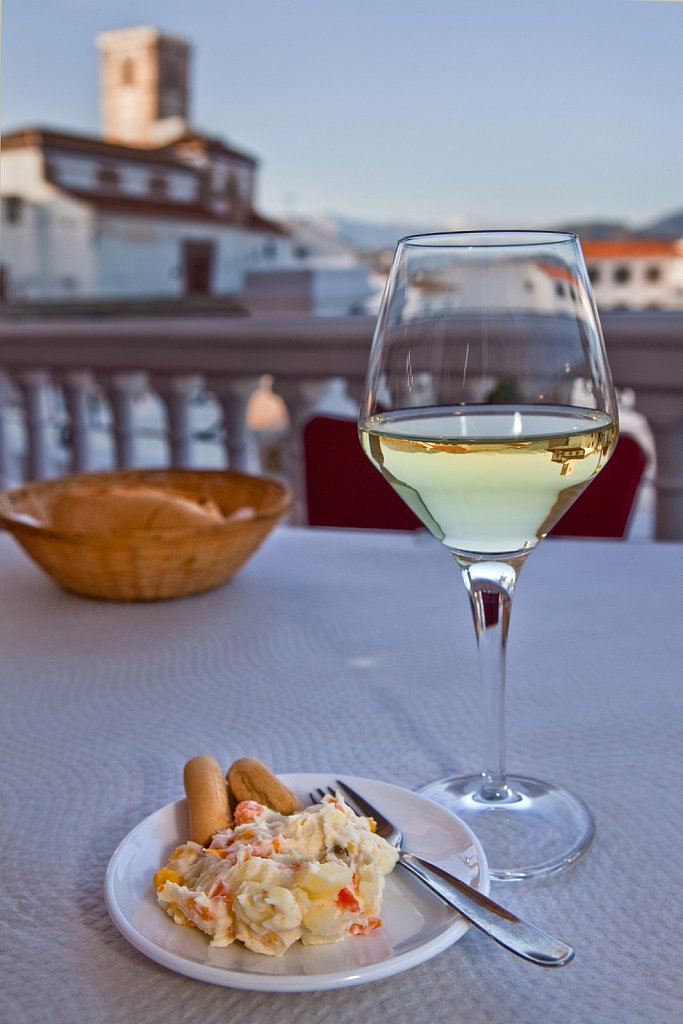 White wine with tapas, potato salad, and bread at restaurant patio in Salobrena, Spain
