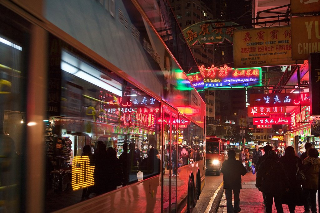 Buses and neon lights in the evening in Kowloon, Hong Kong, China