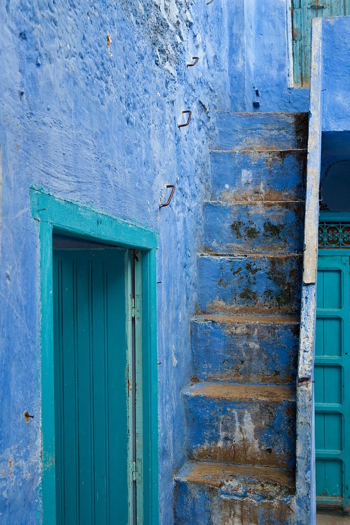 Green door, blue wall and stairs in Chefchouen, Morocco