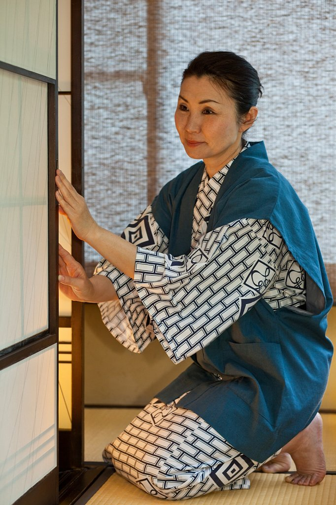 Guest opens shoji screen door at traditional onsen resort in Shizuoka, Japan