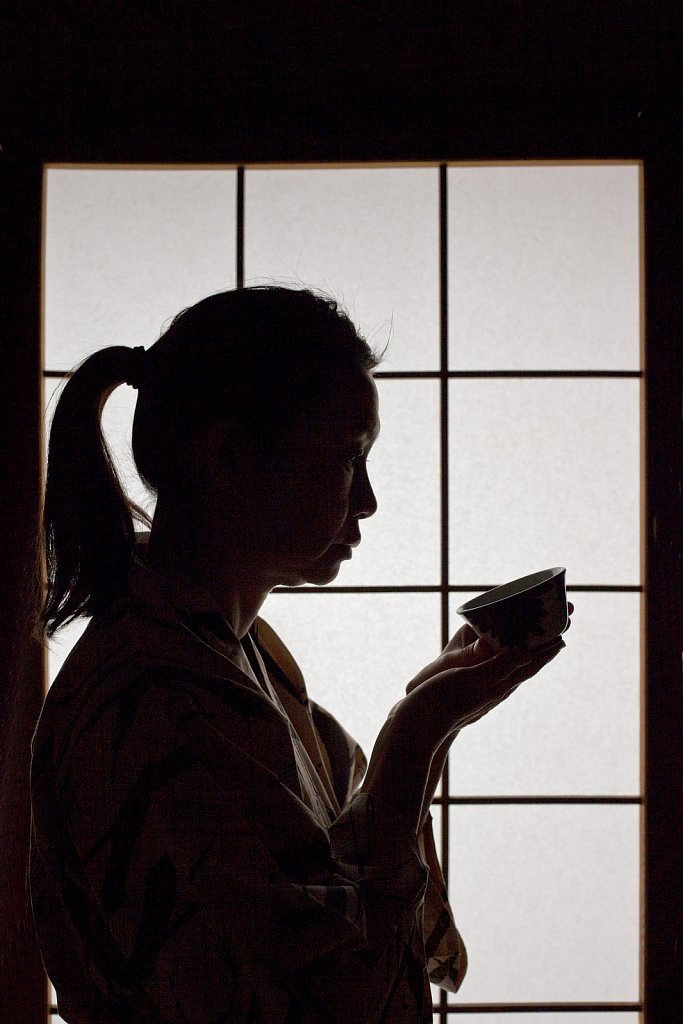 Silhouette of woman with teacup in front of a shoji screen at onsen resort in Mt. Aso, Kyushu, Japan