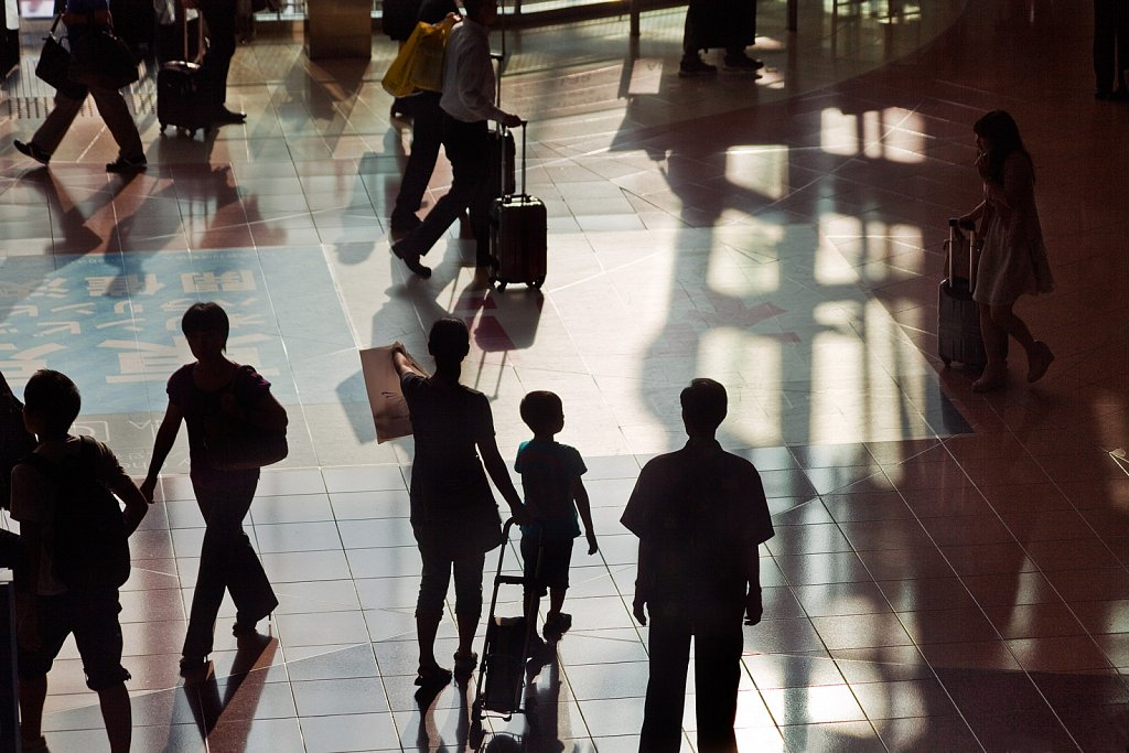 Silhouettes of passengers in the lobby at Haneda Airport, Tokyo, Japan