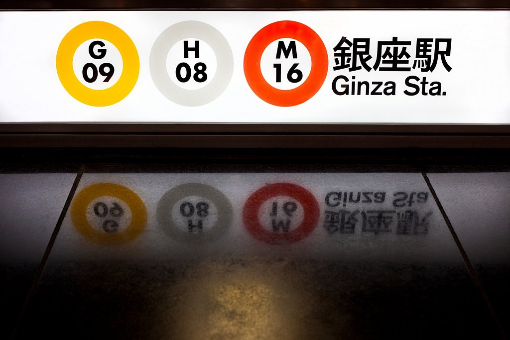 Subway entrance with line signs and reflection at Ginza, Tokyo, Japan