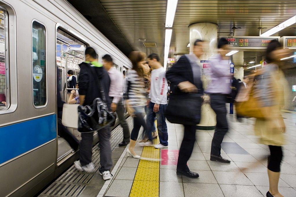 Metro subway train and blur of passengers in Tokyo, Japan